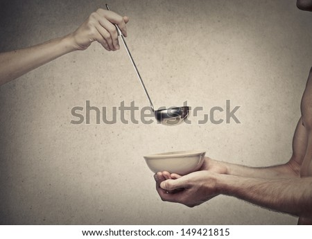 young man waiting with a bowl in his hands the meal - stock photo