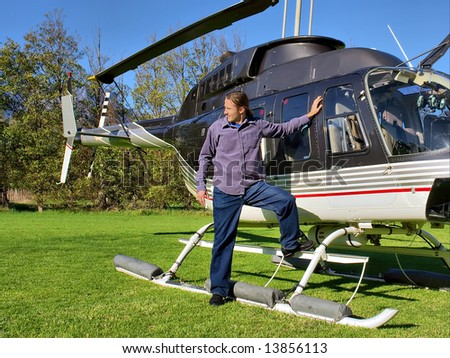 Young man waits next to small private helicopter on grass in estate. Shot  near Cape Town, Western Cape, South Africa. - stock photo
