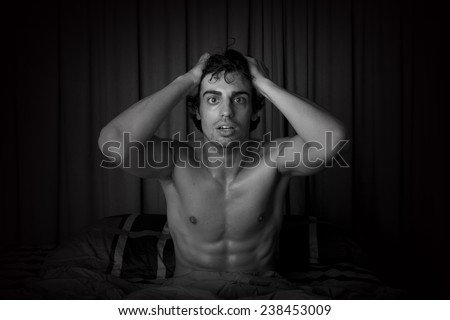 Young man waking up from nightmare - stock photo
