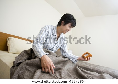 Young man waking up in his bed and looking at the clock