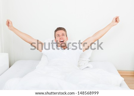 Young Man Waking Up In Morning And Stretching On Bed - stock photo