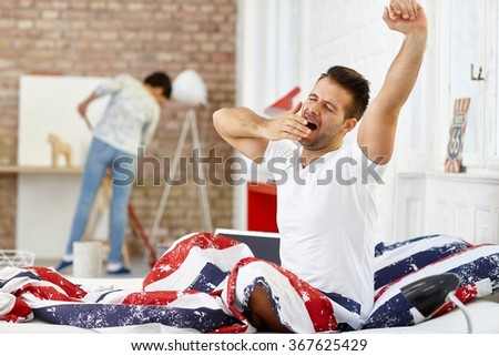 Young man waking up in the morning, yawning and stretching in bed eyes closed. - stock photo