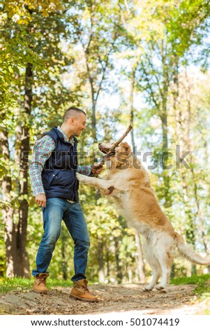 Young man walking a dog at the park in good weather. Boy and golden retriever.
