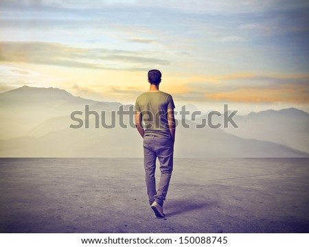 young man walking alone - stock photo