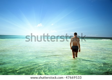 young man walking in Caribbean sea - stock photo