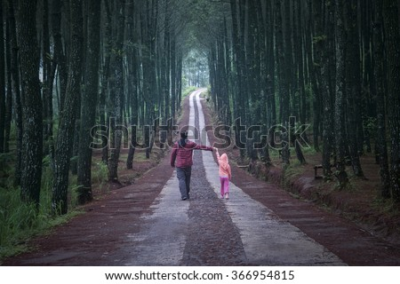 Young man walking in the pine forest while holding hands with his daughter - stock photo