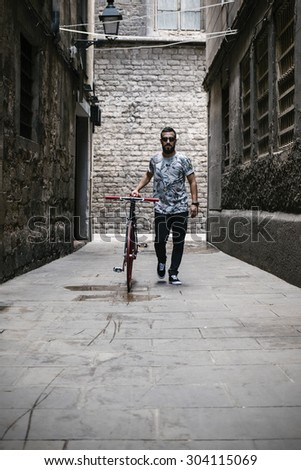 Young man walking in the street with his bike