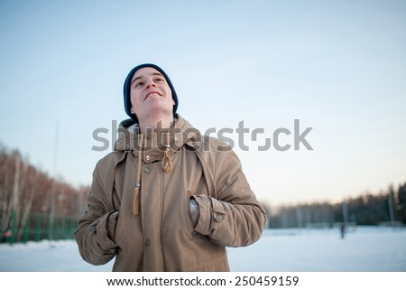 young man walking in the winter park - stock photo
