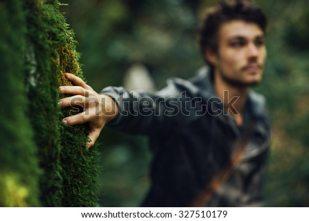 Young man walking in the woods and leaning on a moss covered rock - stock photo