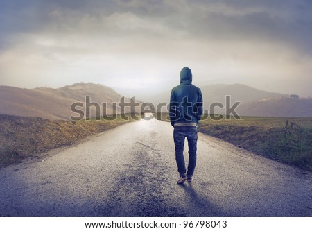 Young man walking on a countryside road - stock photo
