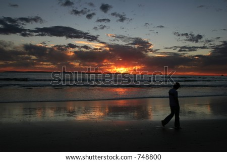 Young man walking on a deserted beach at sunset. - stock photo