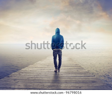Young man walking on a wharf - stock photo
