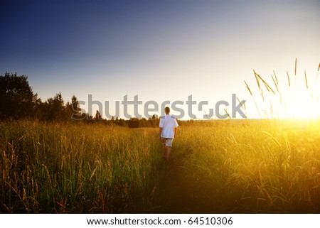 young man walking on field - stock photo