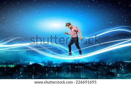 Young man walking on light rays in sky - stock photo