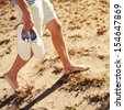 Young man walking on the beach in summer vacation carrying white shoes in hands - stock photo