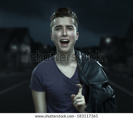 Young man walking on the street the night and sings. Rock'n'roll style. - stock photo