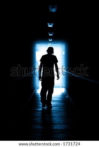 Young Man walking out of the light - stock photo