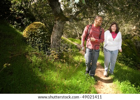 Young man walking with his visually impaired friend on a forest path using sighted guide technique - stock photo