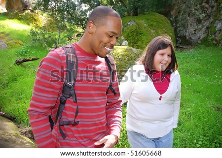 Young man walking with his visually impaired friend through a forest - stock photo