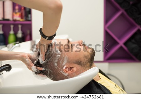 young man washes his head in a hairdressing salon - stock photo