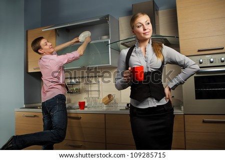 Young man washing dishes and his girlfriend drinking coffee in kitchen - stock photo