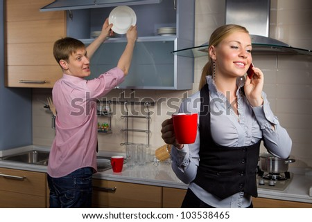 Young man washing dishes and his girlfriend talking by mobile phone in kitchen - stock photo