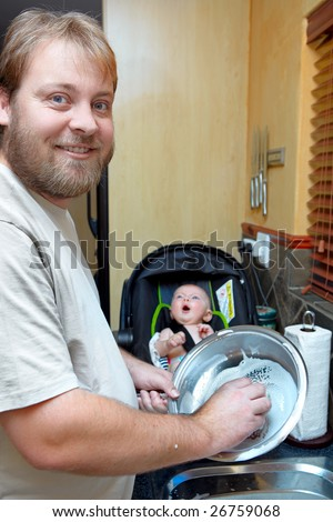 young man washing the dishes with a smile while a baby boy keeps him company in a chair - stock photo