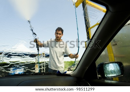 Young man wasing a car using compression water - stock photo