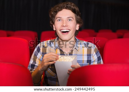Young man watching a film at the cinema - stock photo