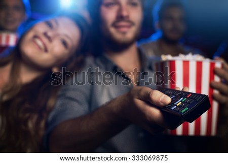 Young man watching a movie with his girlfriend and pointing a remote control: cinema, entertainment and home theater concept - stock photo