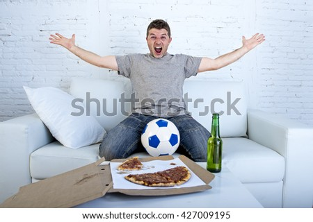 young man watching football game on television celebrating goal crazy happy jumping on sofa couch at home with ball beer bottle and pizza looking excited and cheerful