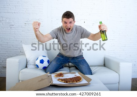 young man watching football game on television celebrating goal crazy happy jumping on sofa couch at home with ball beer bottle and pizza looking excited and cheerful - stock photo