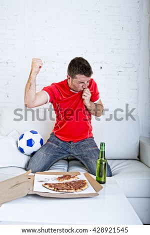 young man watching football game on television kissing team jersey shield celebrating goal crazy happy jumping on sofa couch at home with ball and beer bottle with pizza excited - stock photo