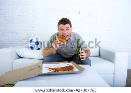 young man watching football game on television sitting on sofa couch with soccer ball at home eating pizza and holding beer bottle looking excited and anxious - stock photo