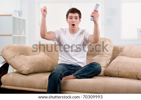 Young man watching football sitting on sofa at home - stock photo