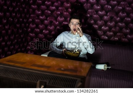 Young man watching scary movie on tv - stock photo