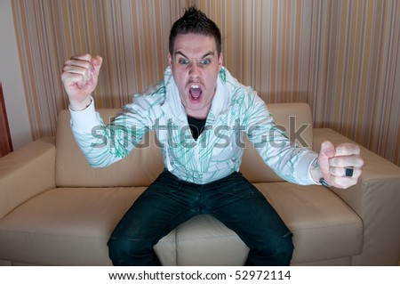 Young man watching television and yelling - stock photo