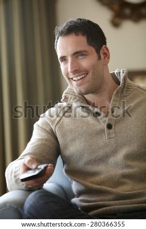 Young man watching television at home - stock photo