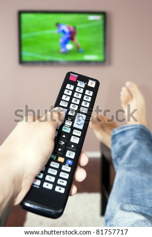 Young man watching the television, the remote control in hand. - stock photo