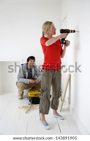 Young man watching woman drill hole in the wall at their new home - stock photo