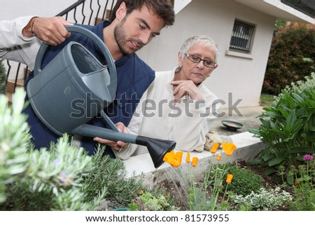 young man watering plants with older woman - stock photo