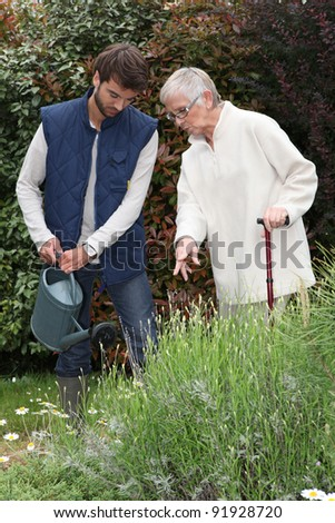 young man watering plants with older woman