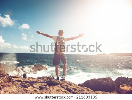 Young man wearing a backpack standing on rocks overlooking the ocean with his arms spread in contemplation backlit by the flare of a hot tropical sun - stock photo