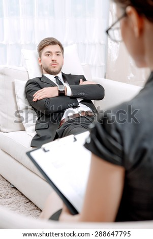 Young man wearing a black suit sitting on a couch crossing his arms looking serious, psychologist with clipboard listening to him and making notes during therapy session, selective focus - stock photo