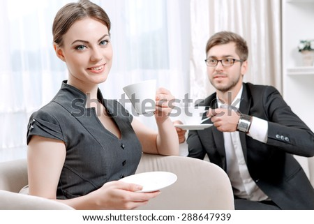 Young man wearing a black suit sitting on a couch drinking tea and talking friendly with his psychologist during therapy session, selective focus - stock photo