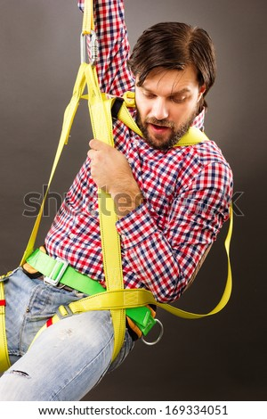 Young man wearing  a fall protection harness and lanyard for work at heights looking down. Gray background - stock photo