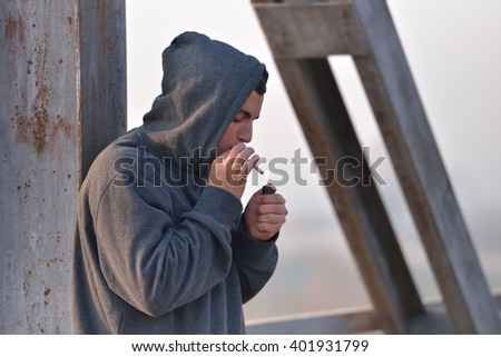 Young man wearing a hoodie standing by a bridge and lighting a cigarette. Unhealthy habits. Selective focus - stock photo