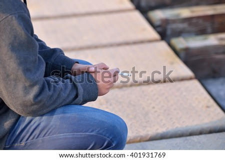 Young man wearing a hoodie standing by a bridge and smoking a cigarette. Unhealthy habits. Selective focus - stock photo