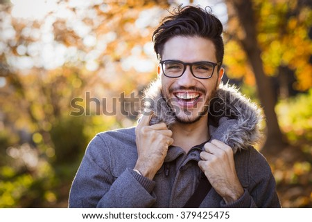 Young man wearing a jacket with a hood in a cold autumn day - stock photo