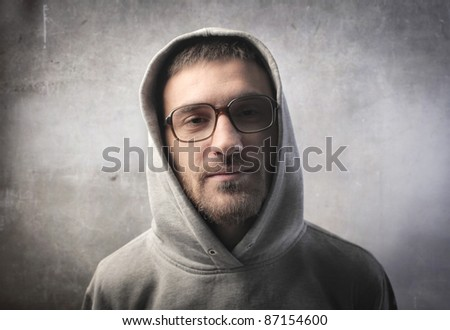 Young man wearing a sweater with a hood - stock photo